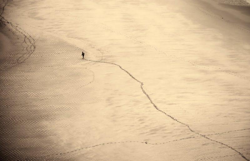 маленький человечек идёт по песку морского пляжа прочерчивая диагональ следов small man walking on the sea shore автор Демидов Игорь