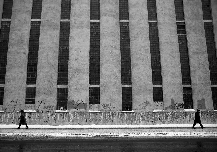 grey walls small figures walking away people высокие серые стены маленькие фигуры людей идущие в разные стороны