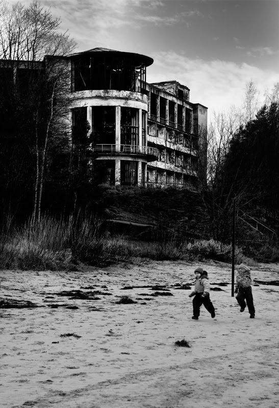 дети бегут по песку пляжа мимо разрушенного бетонного санатория автор Демидов Игорь children running on the shore sand near the destructed sanatorium