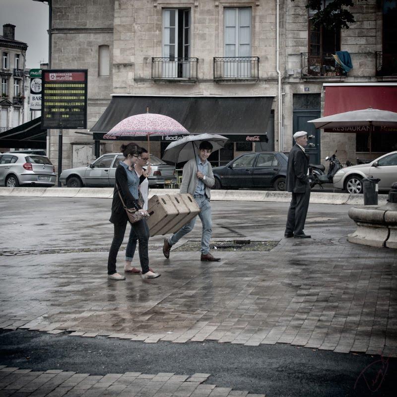 people hanging trunk under rain in Bordeaux молодежь тащит чемодан под дождем в Бордо автор Демидов Игорь