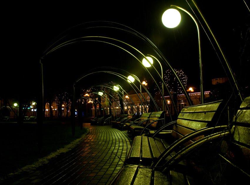 Фонари и скамеечке ночью под дождём на площади рядом с Jomas iela street lamps and benches at night under falling rain