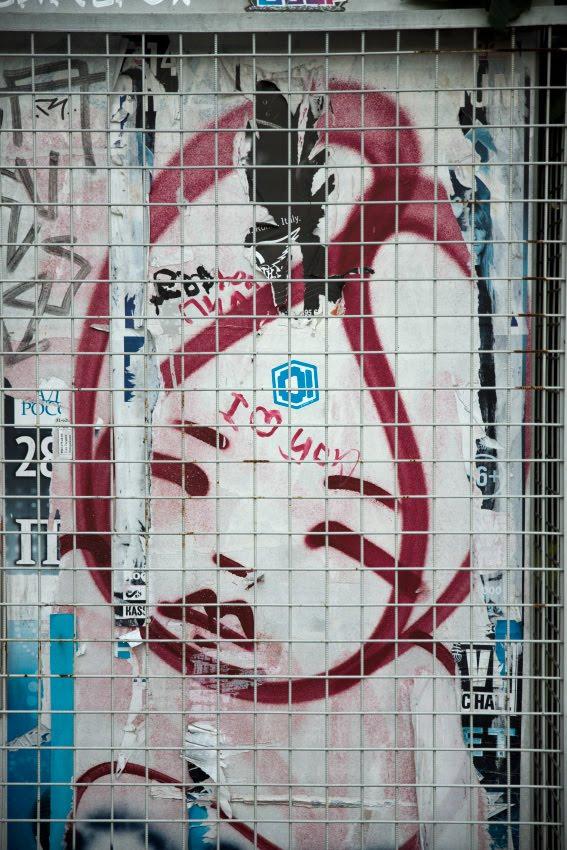 печальное лицо за стальной решеткой уличное искусство автор фото Демидов Игорь street art sad face beyond fence