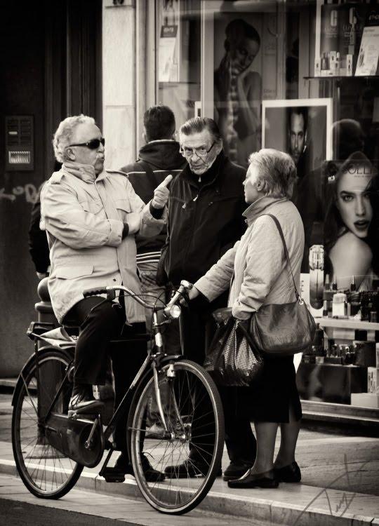 Группа пожилых людей на улице Пармы оживлённо обсуждает чтото, усатый человек на велосипеде жестикулирует и говорит автор Демидов Игорь group of old people talking on the street man with moustaches