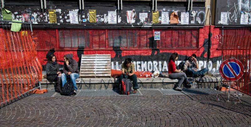Turin (Torino) students sitting near graffiti red wall  Туринские студенты сидят под стеной на стене тени ходят и тянут за веревки автор Демидов Игорь
