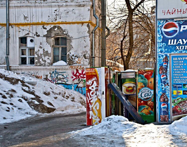 серые стены и снег цветные ларьки реклама граффити труба автор Демидов Игорь grey snow walls colorful kiosk graffity and yellow pipe