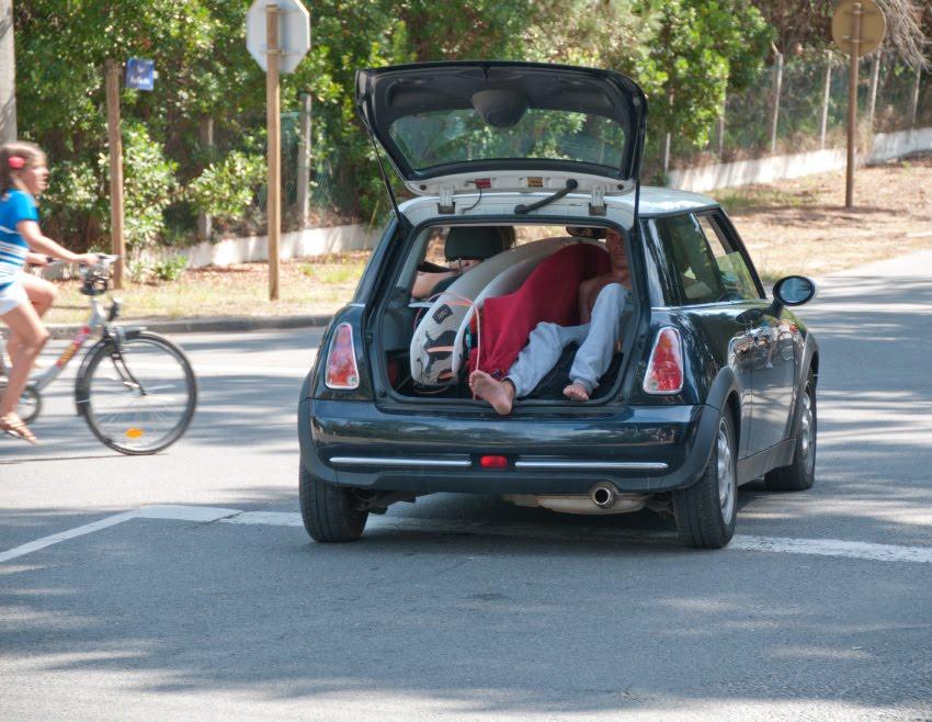 Surfer in a trunk of mini cooper серфер катается в багажнике мини купера девочка на велосипеде переезжает дорогу автор Демидов Игорь