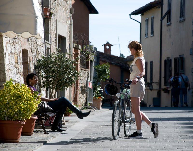 утренняя беседа белой велосипедистки и чёрной женщины на скамейке автор Демидов Игорь morning conversation of two women one on th bench another with bicycle