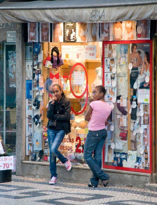 девушки стоят вдвоём у магазина нижнего белья вечером в лиссабоне автор Демидов Игорь two girls standing near the lingerie shop evening in Lisbon