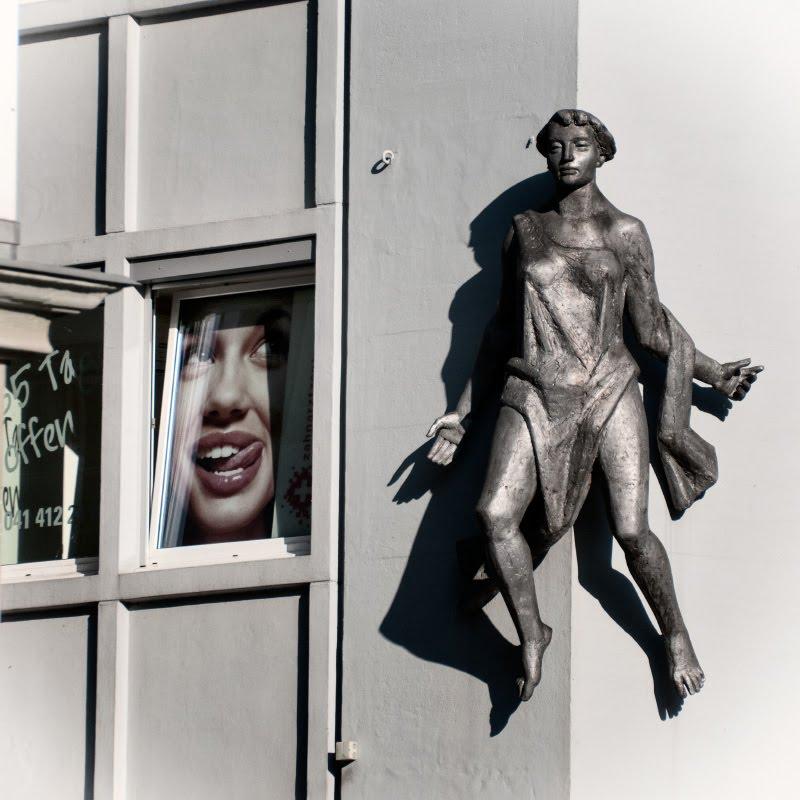 девушка в окне облизывает губы смотрит на статую на углу дома автор Демидов Игорь woman in window lick her lips looking at other girl on the corner of the building