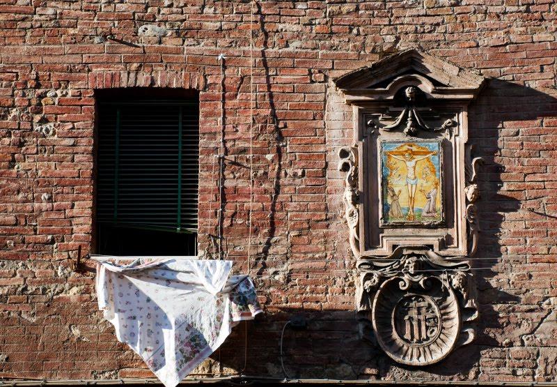 Siena window and icon on the street wall with wet linen между окном и иконой на кирпичной стене Сиены натянута тряпка для сушки белья автор Демидов Игорь